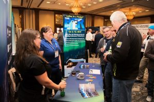 BER Employees talking to attendees at the annual RESNET conference. The photo also shows marketing materials and booth design with BER branding.