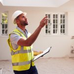 A man wearing a hardhat inspects a newly constructed home.